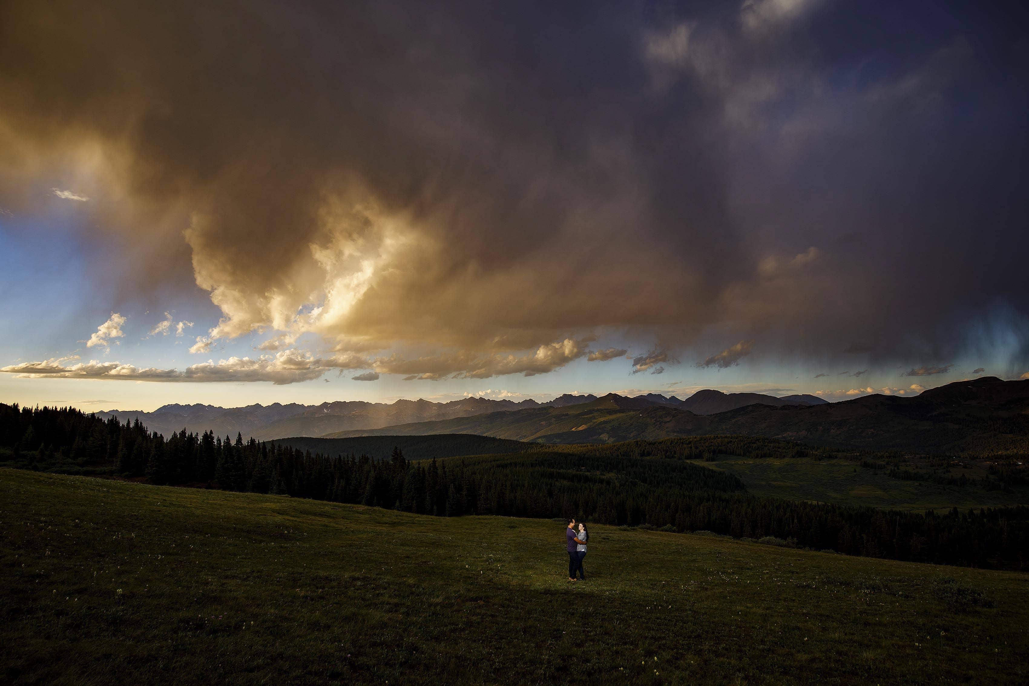 Mike and Courtney share a moment together atop Shrine Pass as the sun sets over the Gore Range near Vail, CO during their engagement session