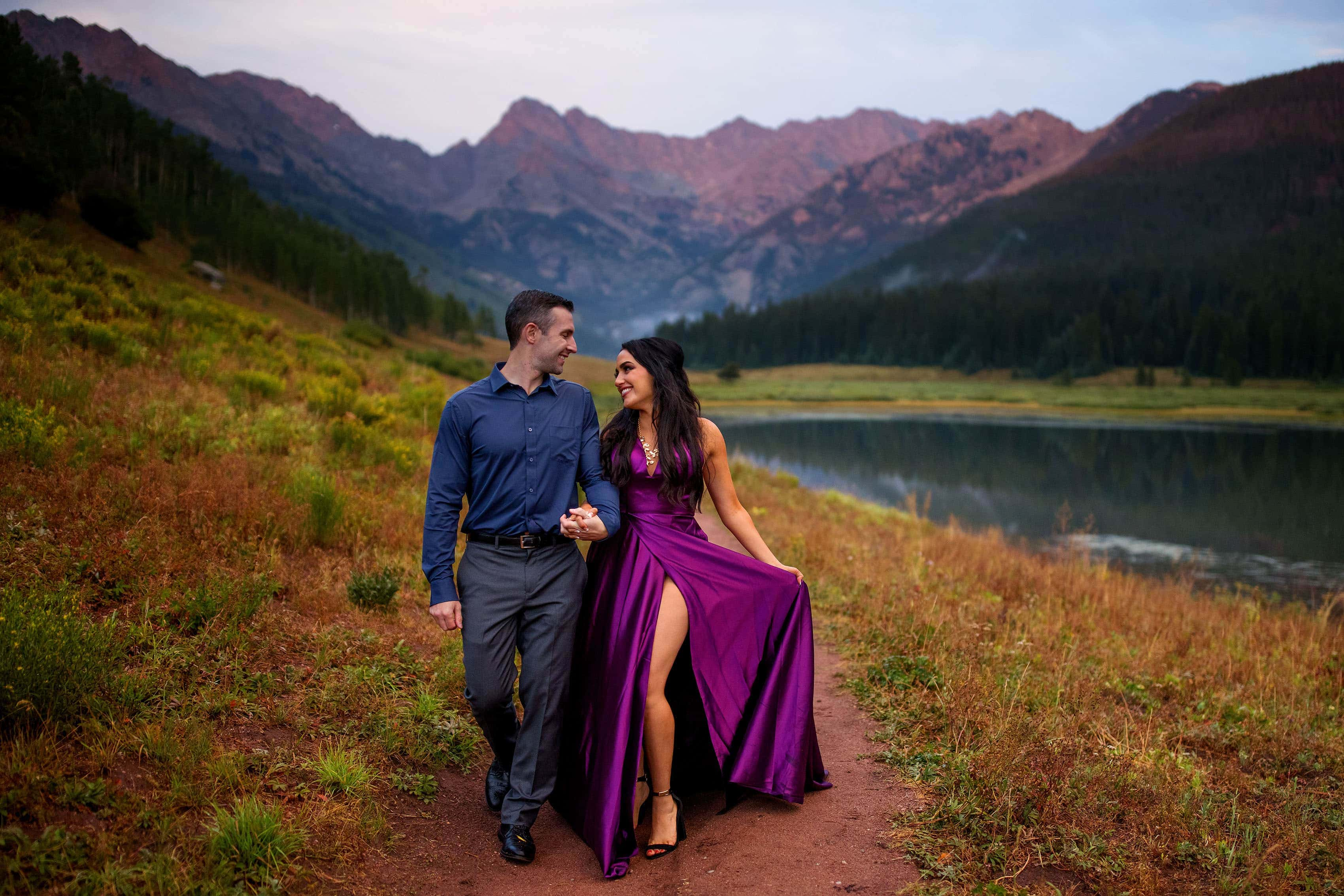 Maggie holds her purple gown as the alpenglow hits the Gore Range during their engagement photos at Piney Lake