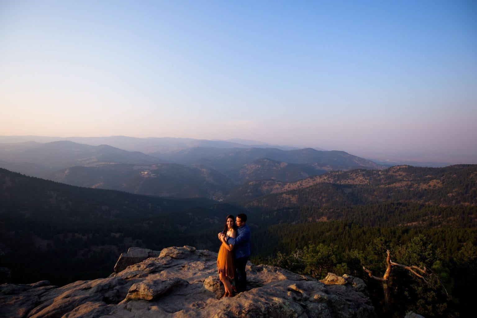 Briana and Tim embrace atop Lost Gulch Lookout during their engagement photos in Boulder