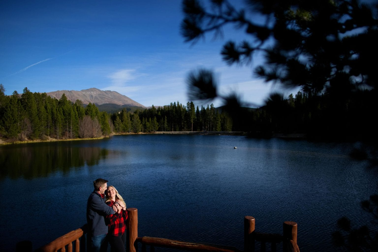 Joseph and Chloe share a moment on the dock at Sawmill Reservoir in Breckenridge during their engagement photos