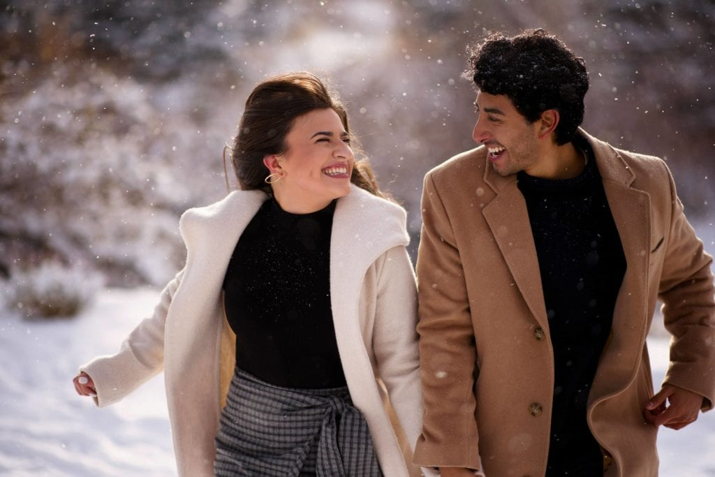 A couple runs in the snow during their winter wonderland engagement in Breckenridge