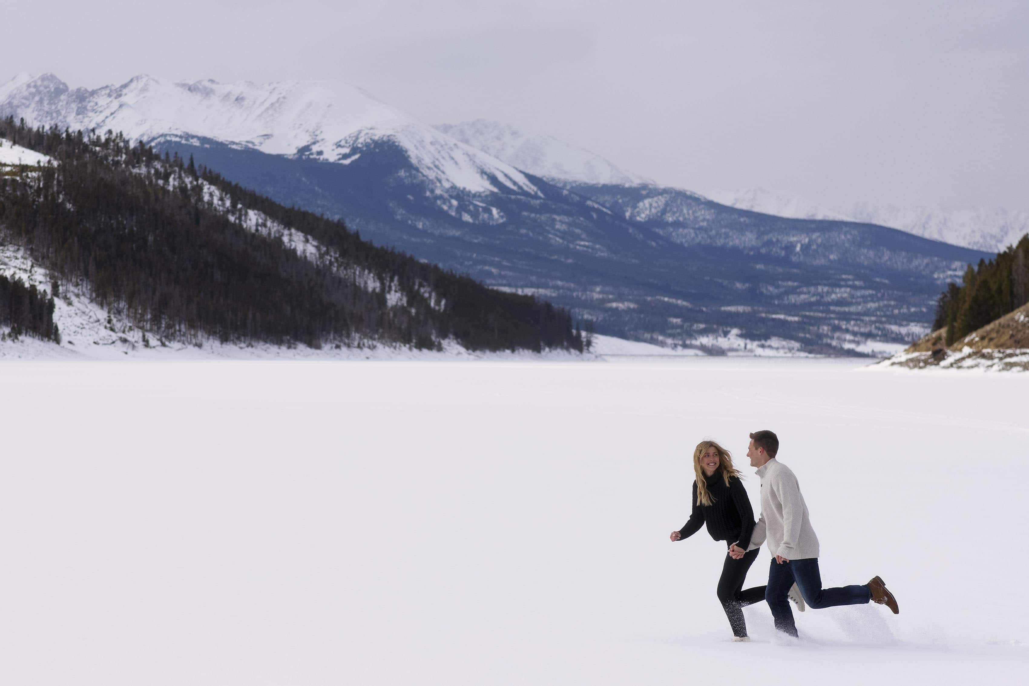 Kayla and Scott run in the snow on frozen Lake Dillon during their engagement photos