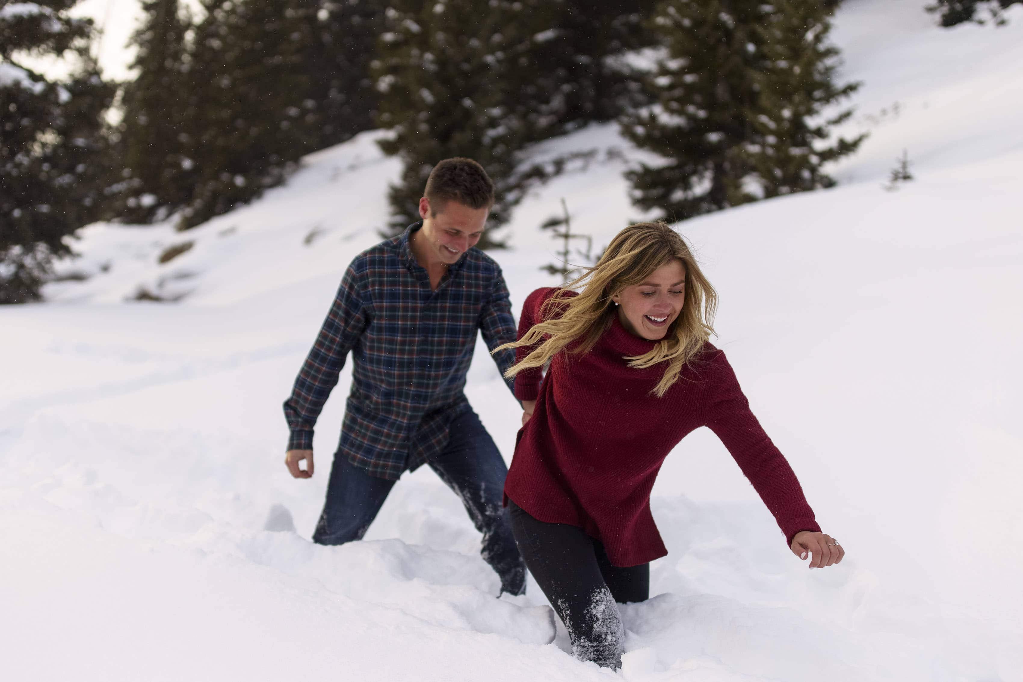Kayla helps pull Scott through deep snow during their winter engagement photos near Loveland Pass