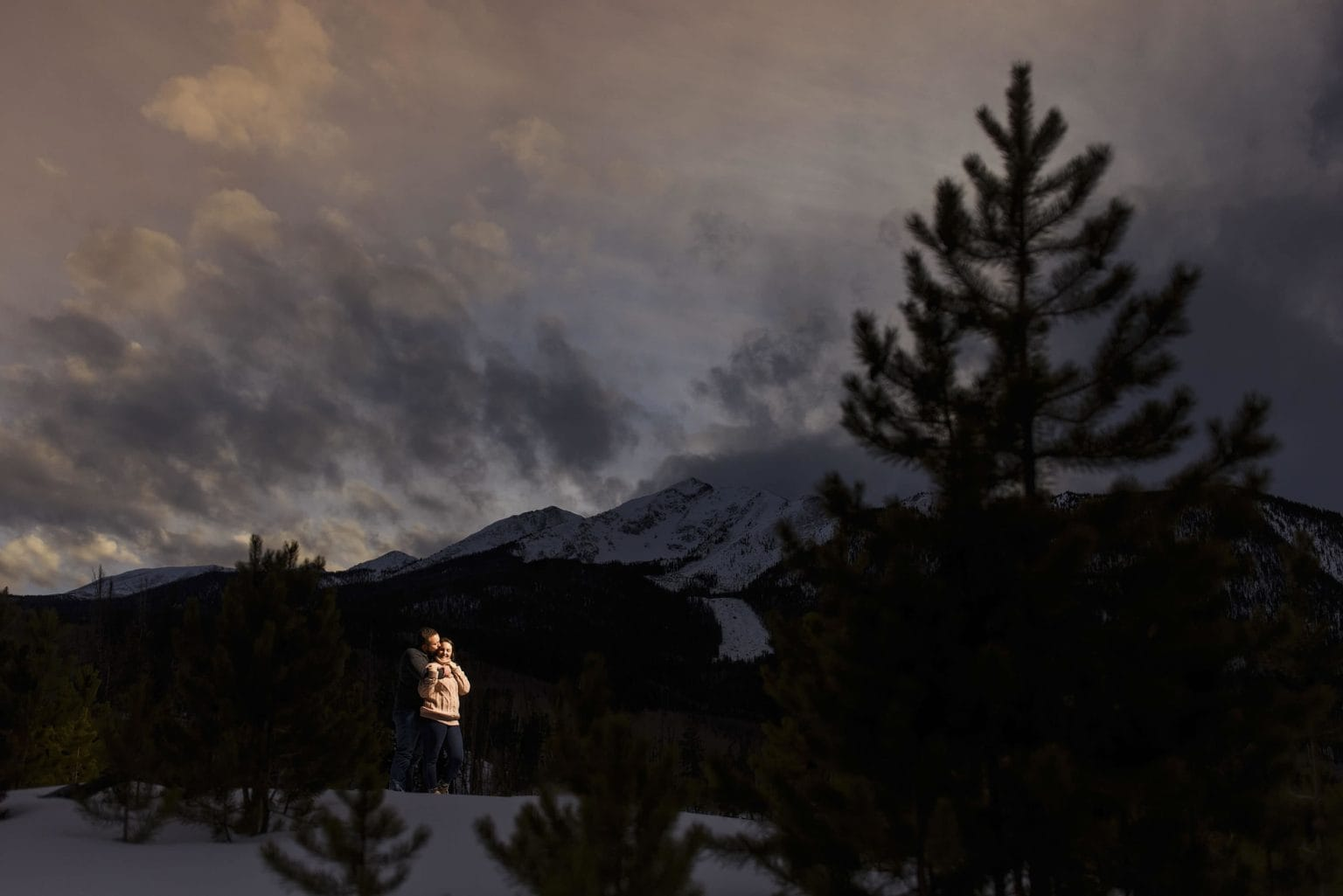 Nick kisses Bethany as the sun sets over Peak 1 in the Tenmile Range in Frisco during their engagement photos