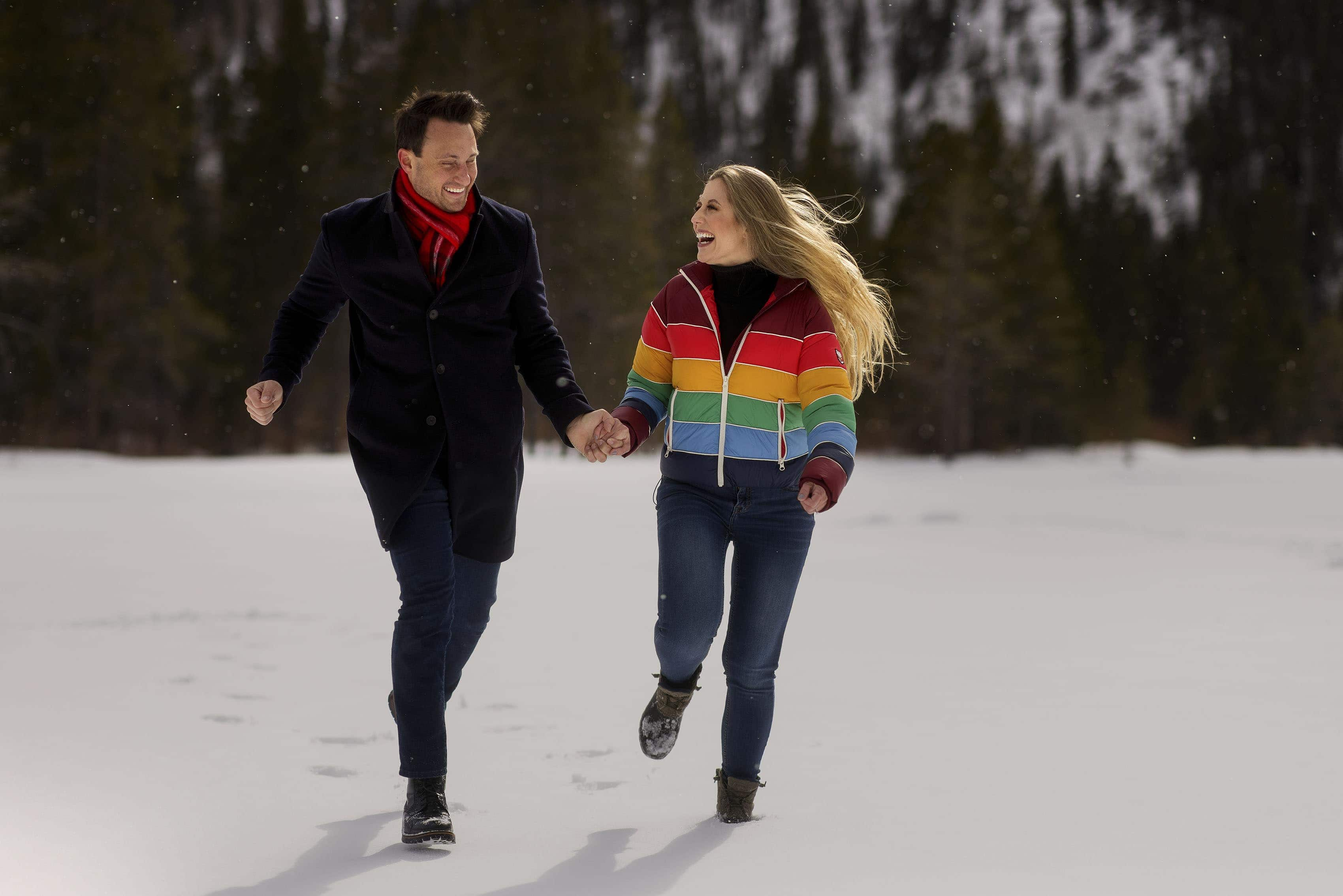 Brad and Nicole run and laugh in the snow during their snowy summit county engagement photos at Officers Gulch