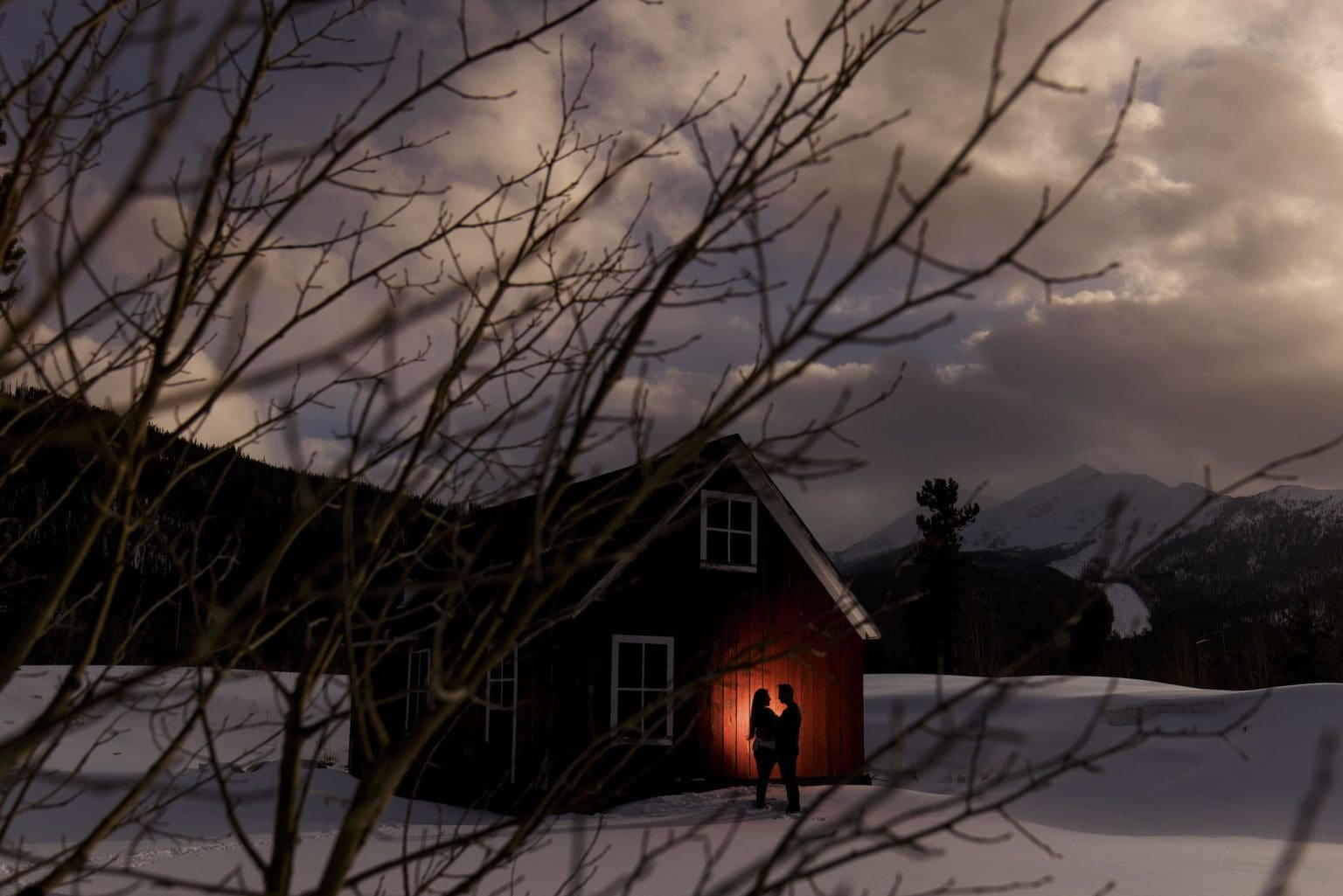 A couple is silhouetted against a red barn in the snow near Frisco, CO