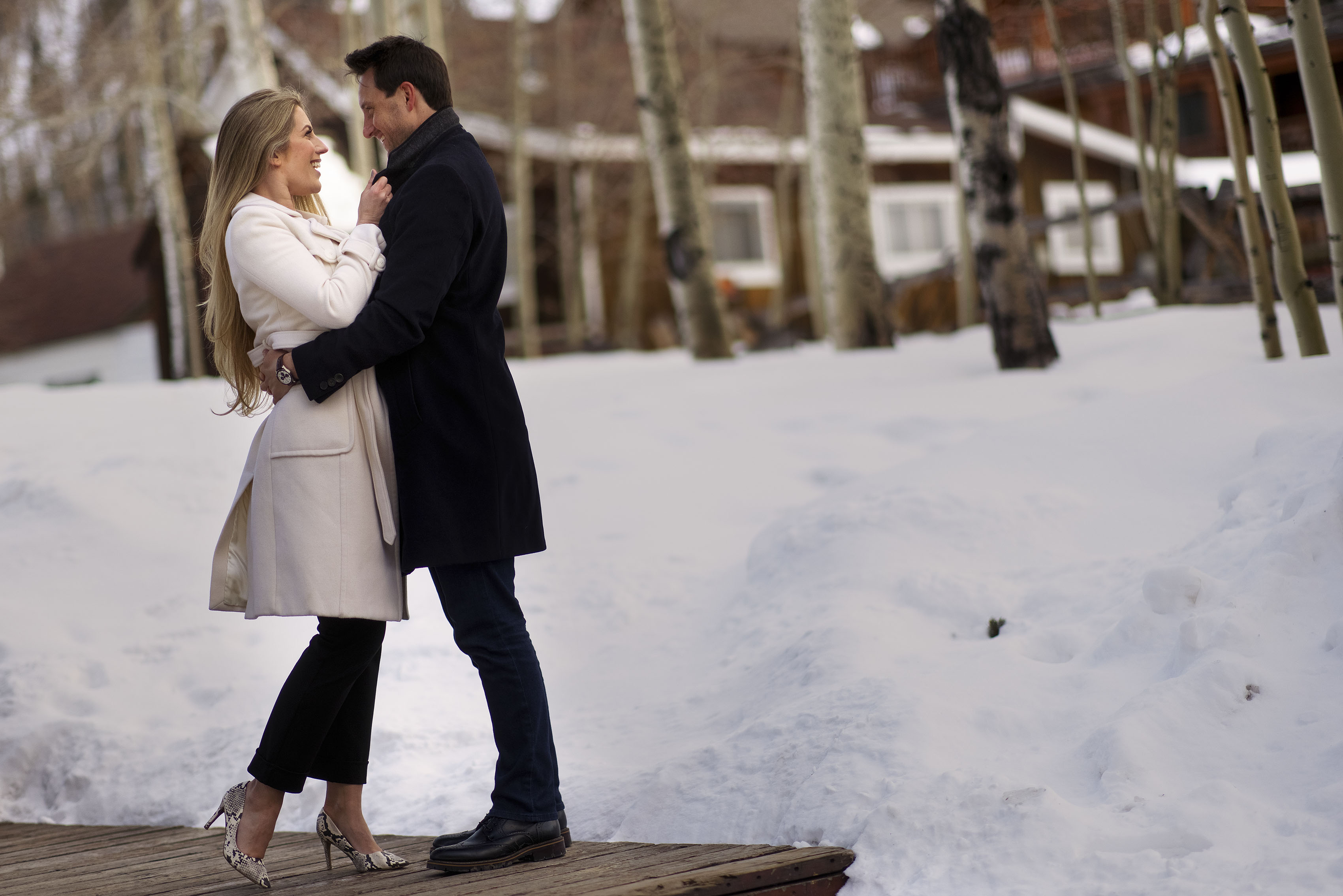 A fashionable couple stand near a snowy courtyard in downtown Frisco during their engagement photos