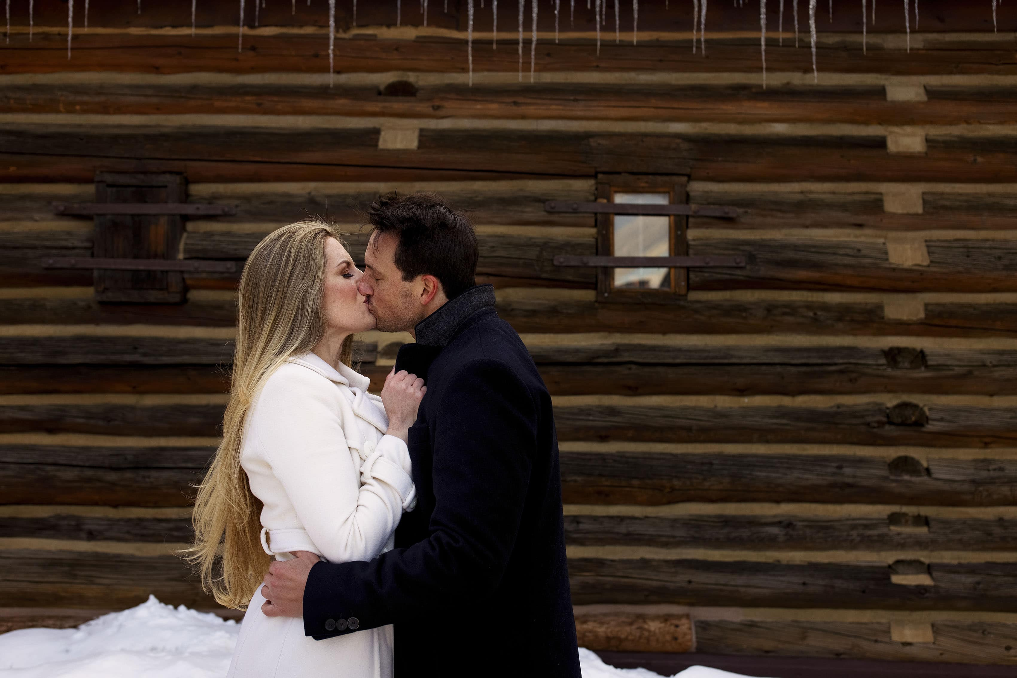 Nicole and brad stand under ice cicles and share a kiss in Frisco, CO