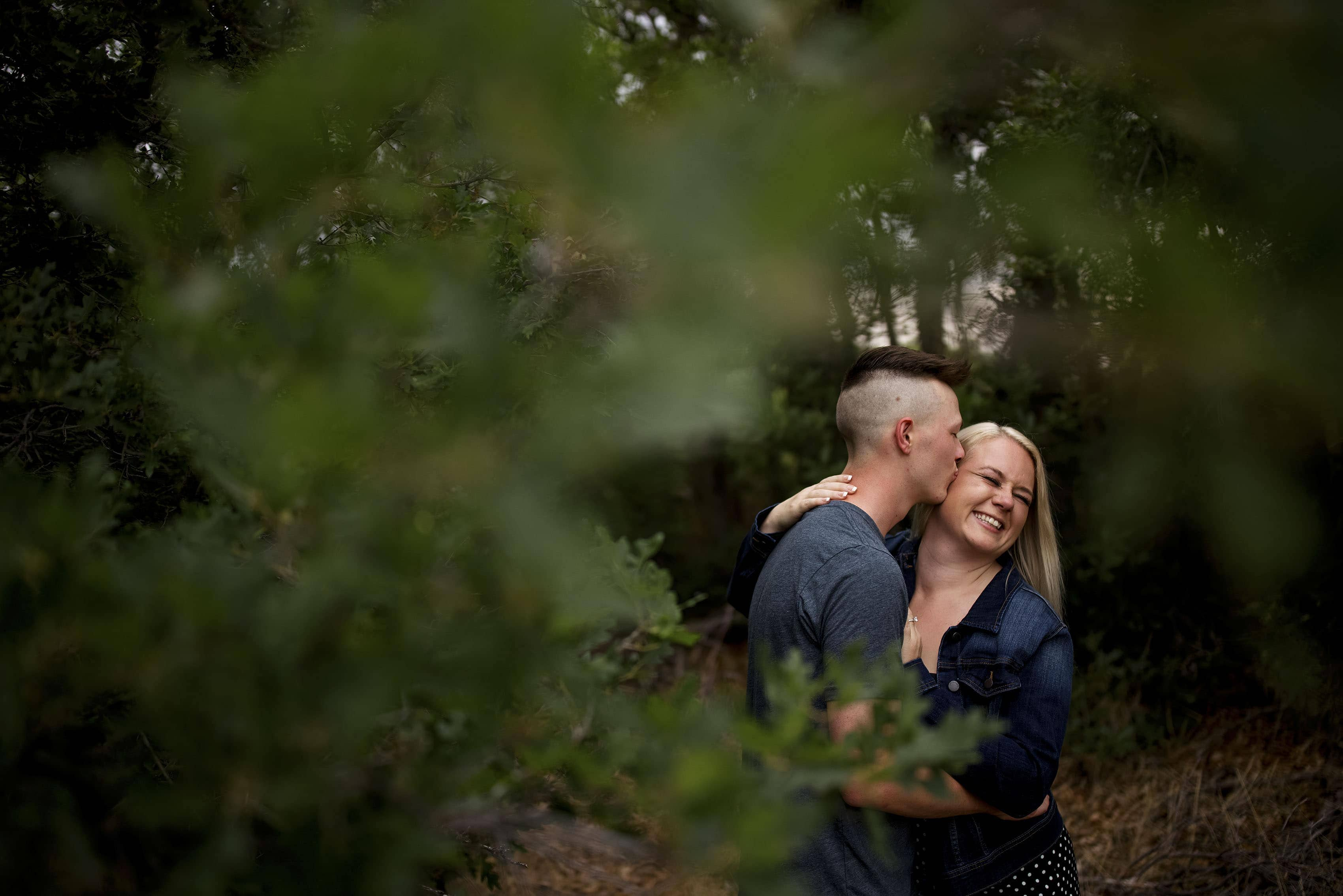 Colin kisses Kelsey in the woods during their engagement photos