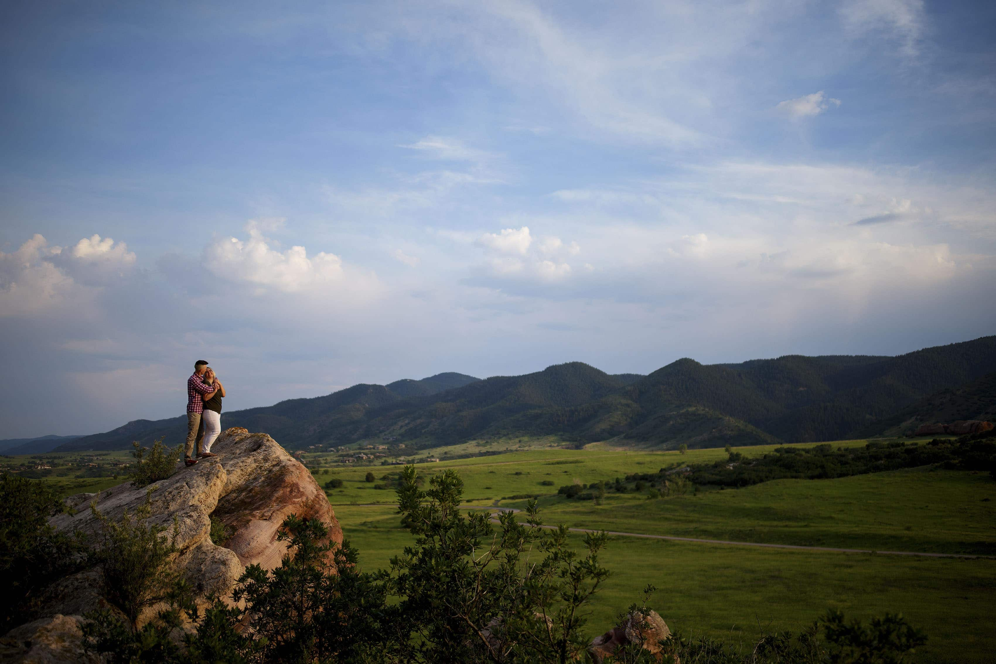 Kelsey and Colin stand on a rock formation in Littleton during their engagement session