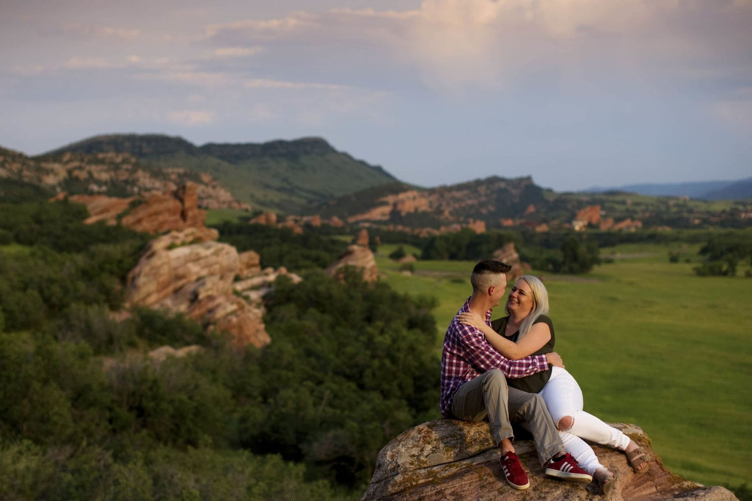 Colin and Kelsey sit on a natural rock formation during their engagement photos in Littleton