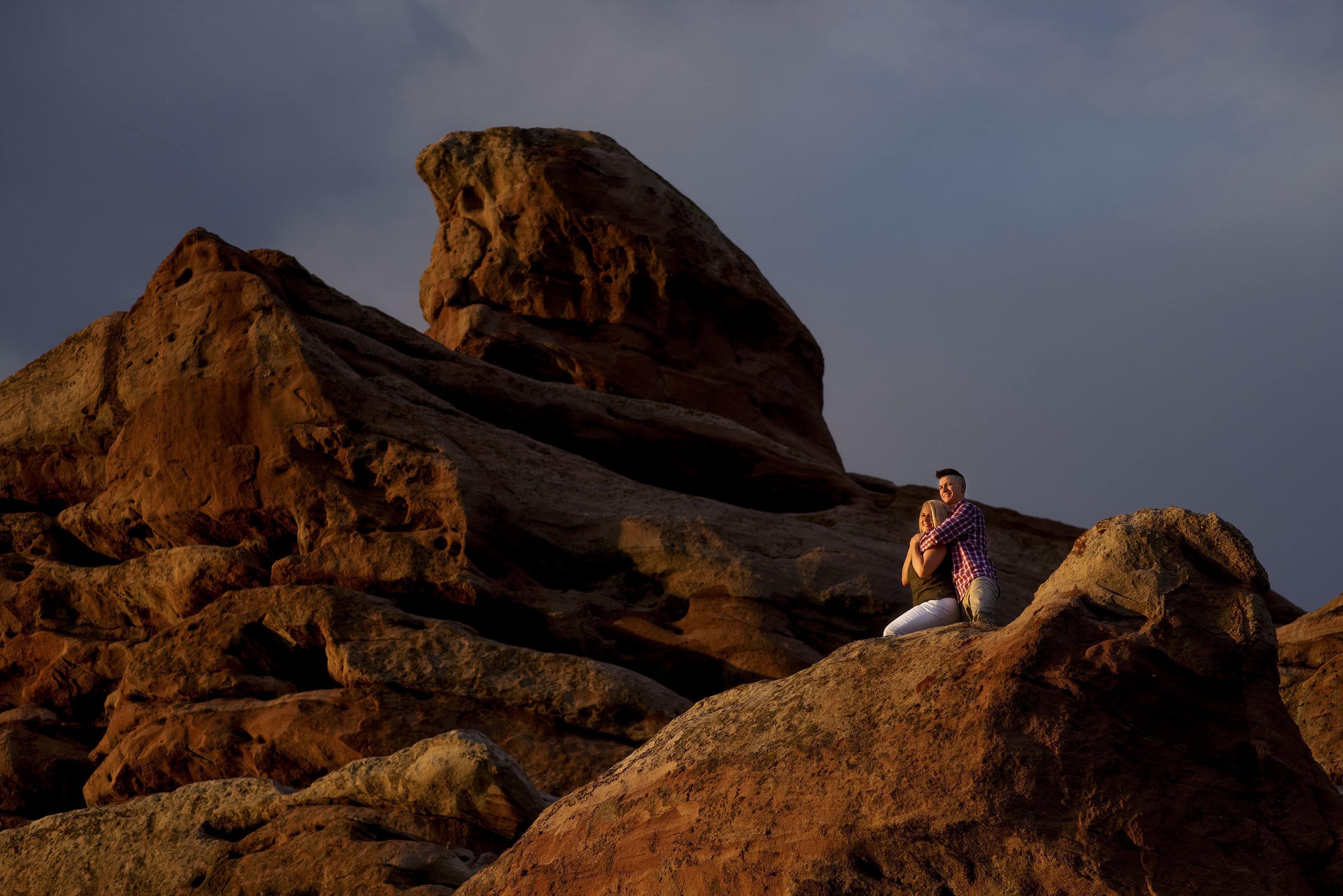 Kelsey and Colin pose on a red rock formation during their engagement session