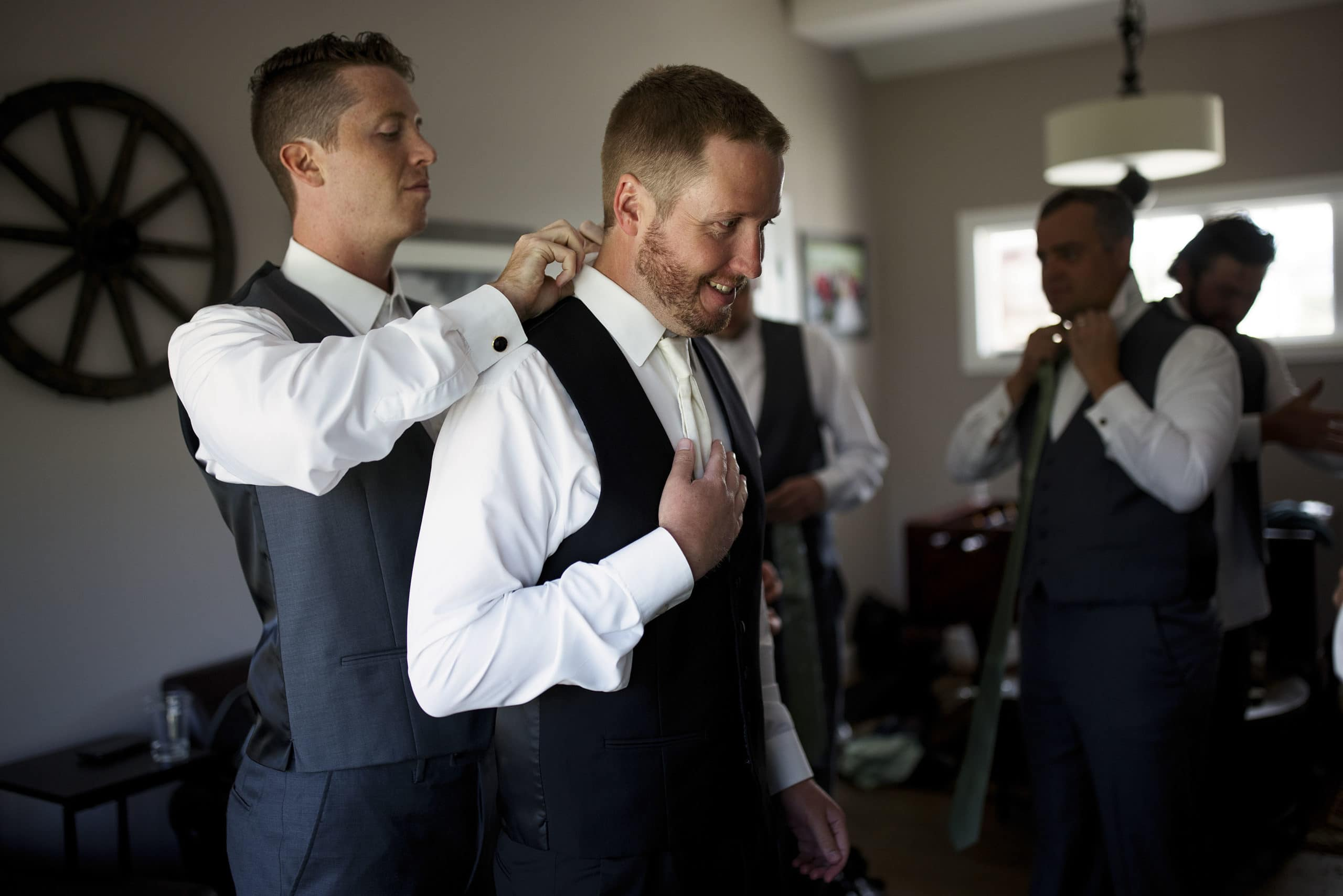 Stefan gets help with his tie while getting ready before the wedding