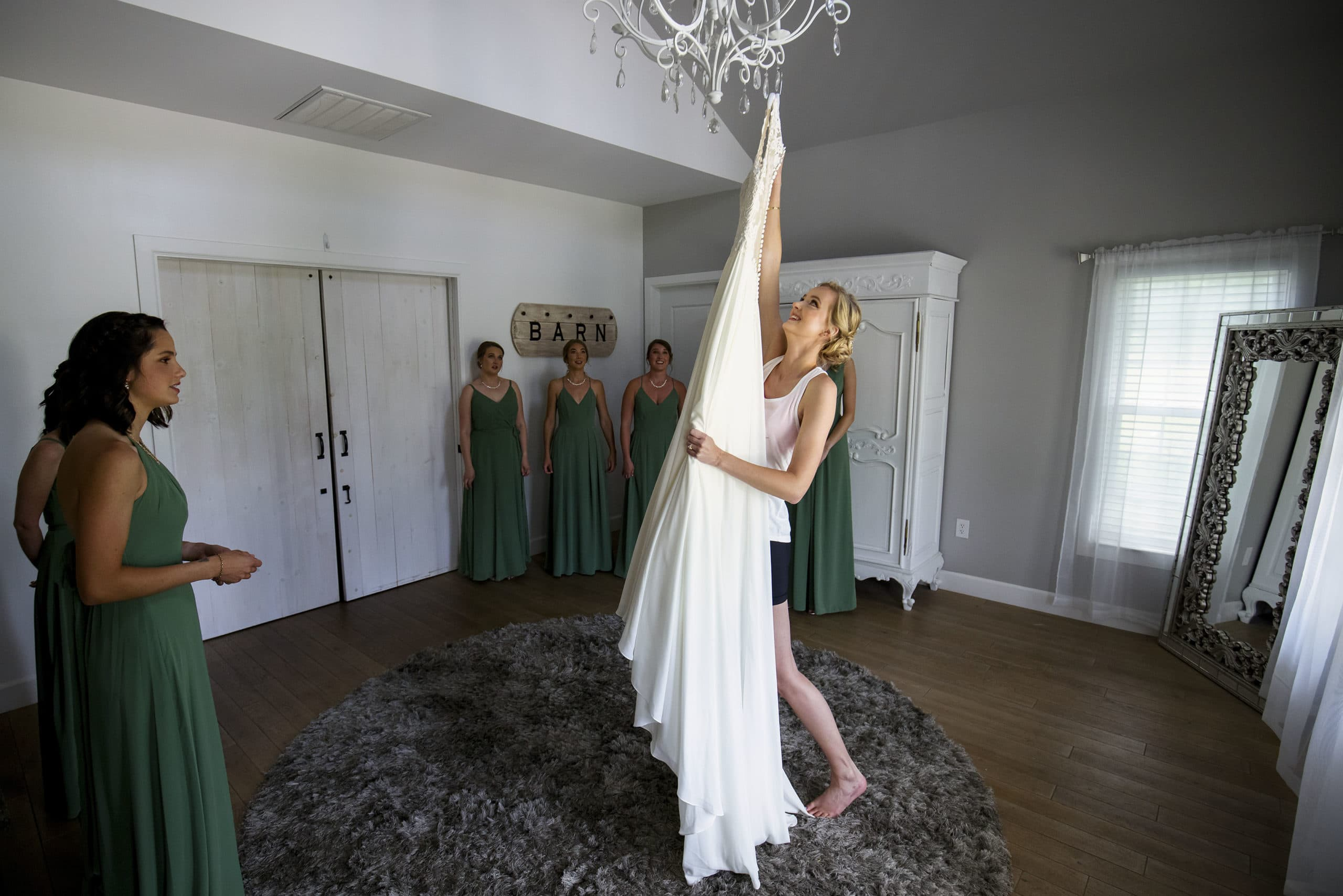Jennifer reaches up to remove her wedding dress from the chandelier