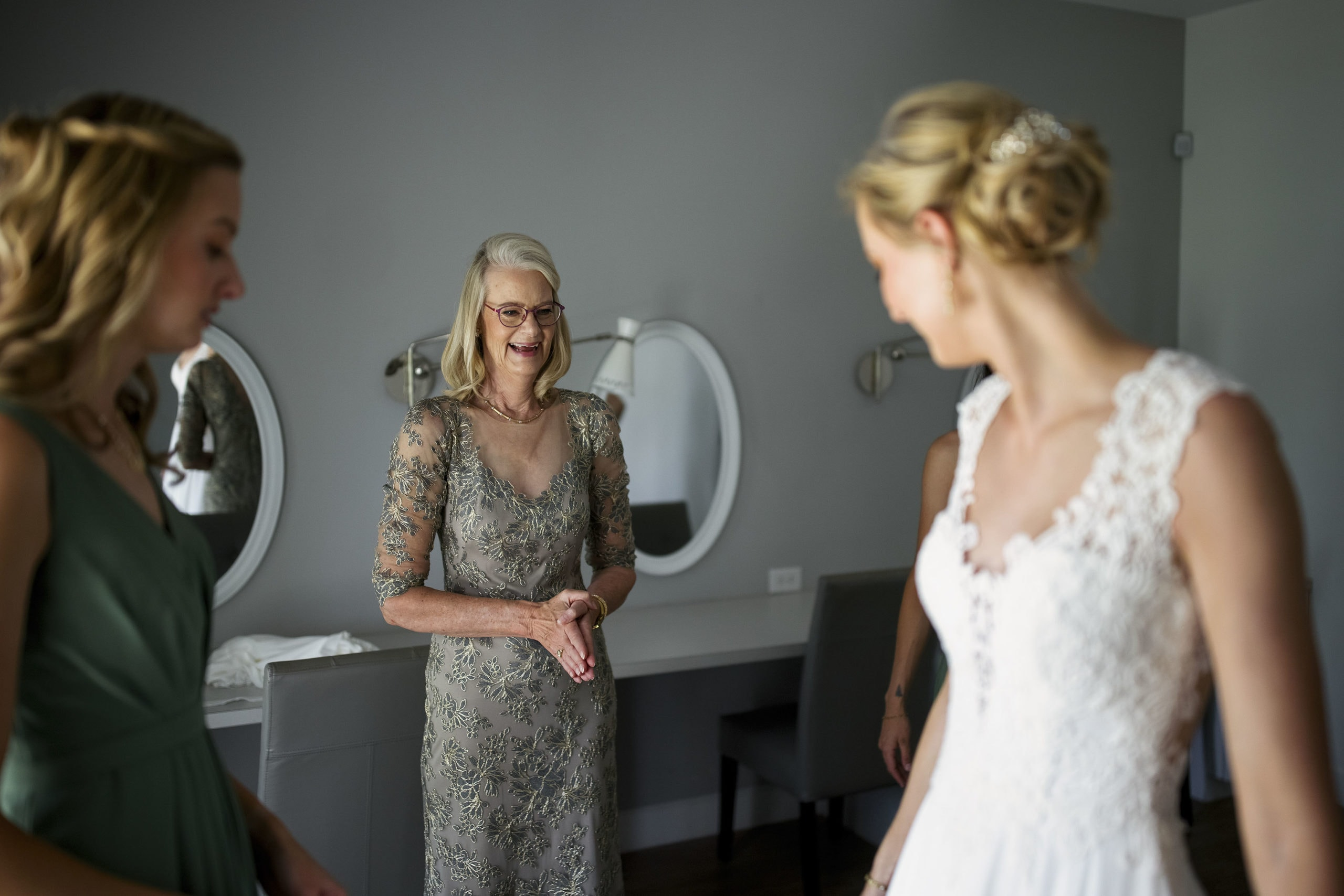 The mother of the bride reacts after Jennifer finishes putting on her wedding dress