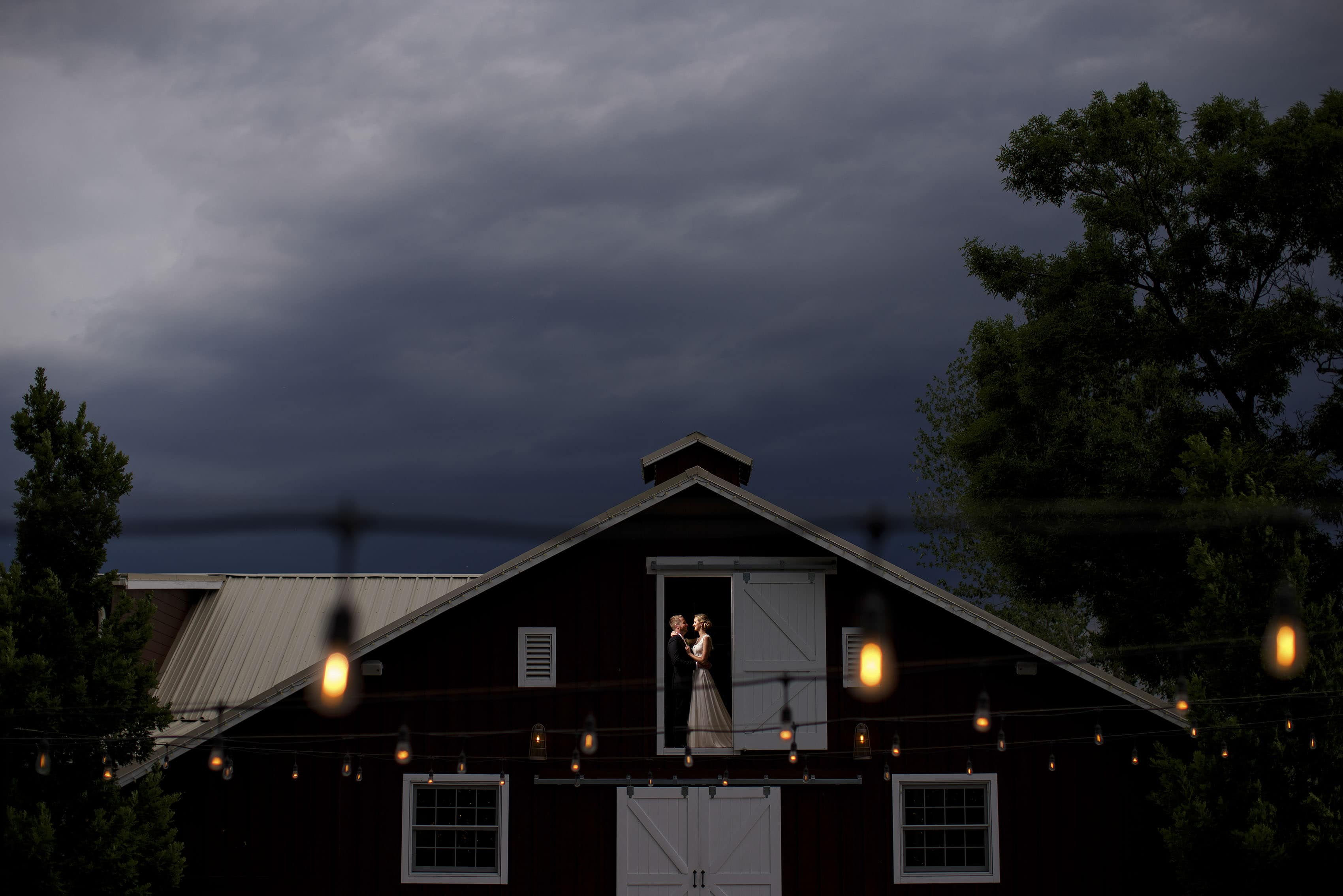 Jennifer and Stefan pose in the barn loft during their wedding day at the barn at raccoon creek in Littleton