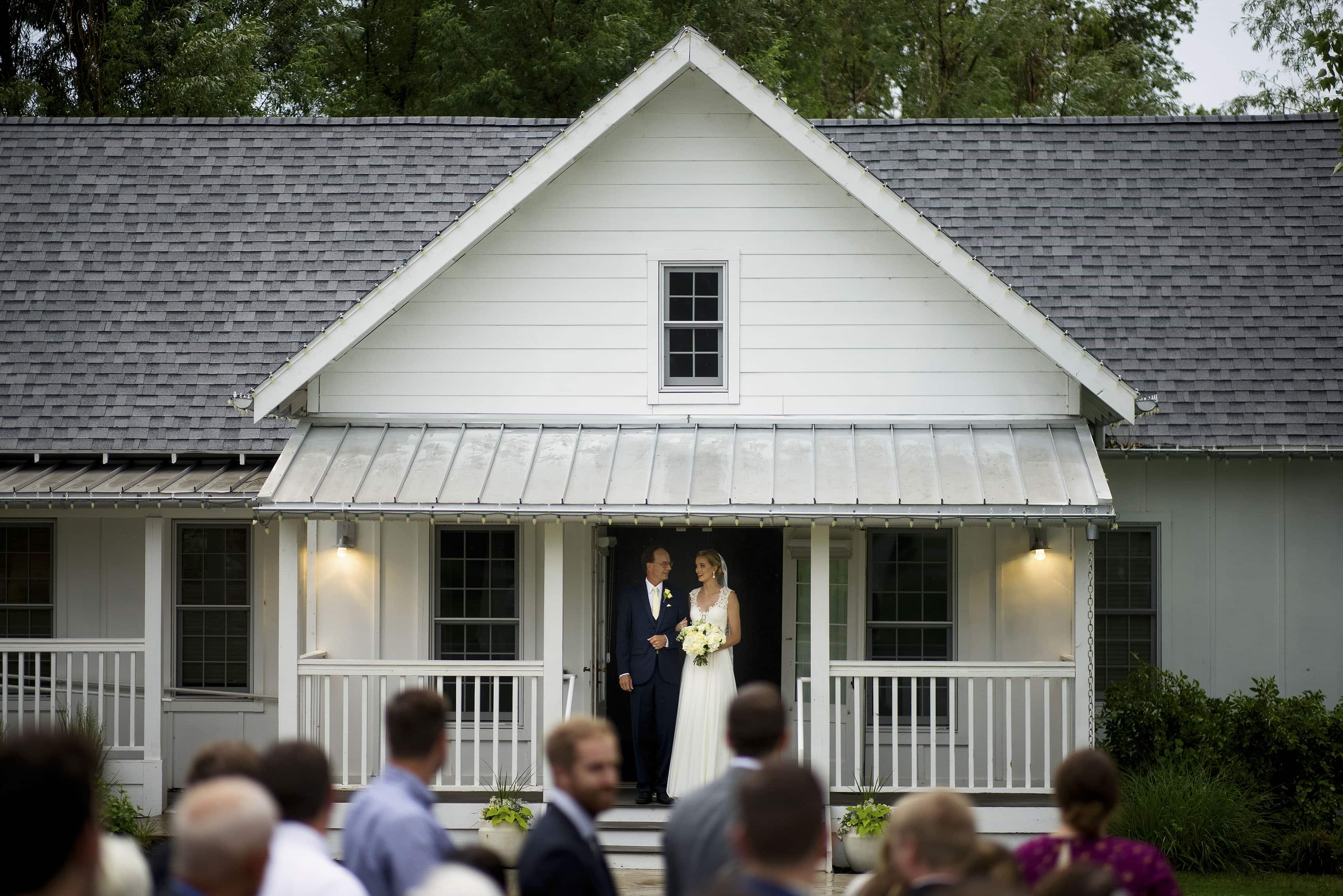 The bride and her father exit the bridal cottage during the wedding ceremony at the barn at raccoon creek