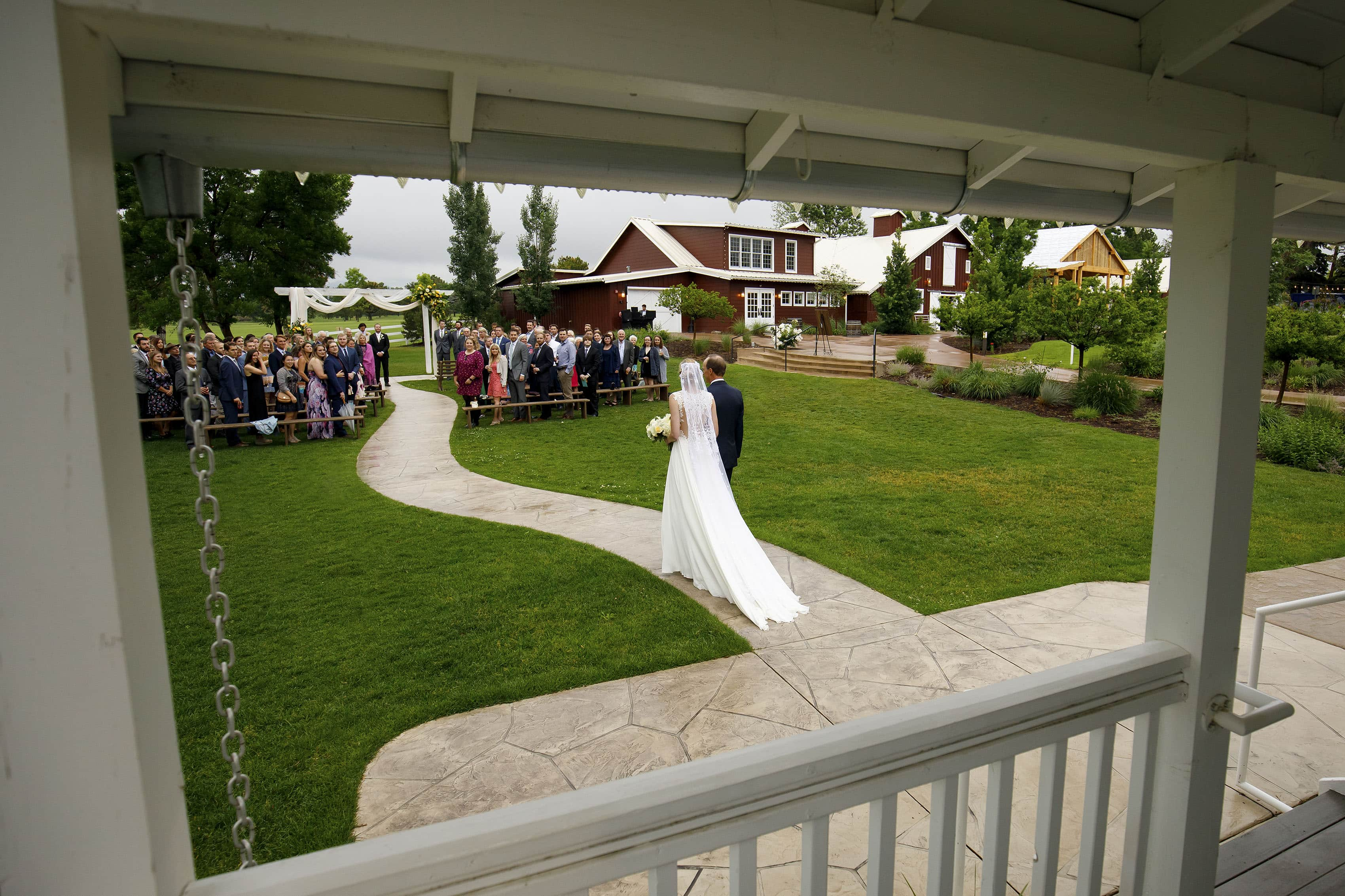 The bride walks down the aisle with her father at the barn at raccoon creek in littleton