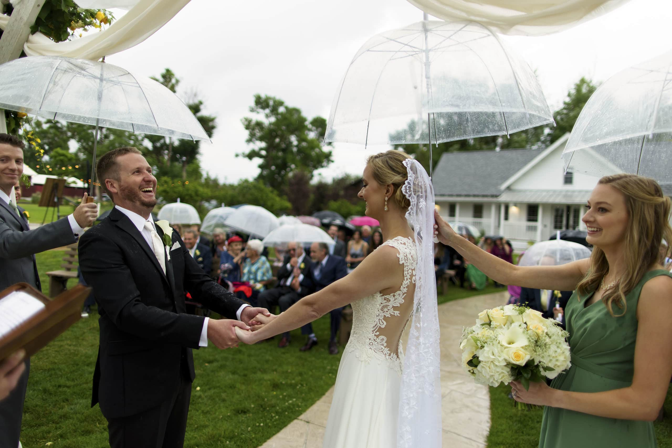 The couple react as umbrellas shield them as rain begins to fall during the ceremony