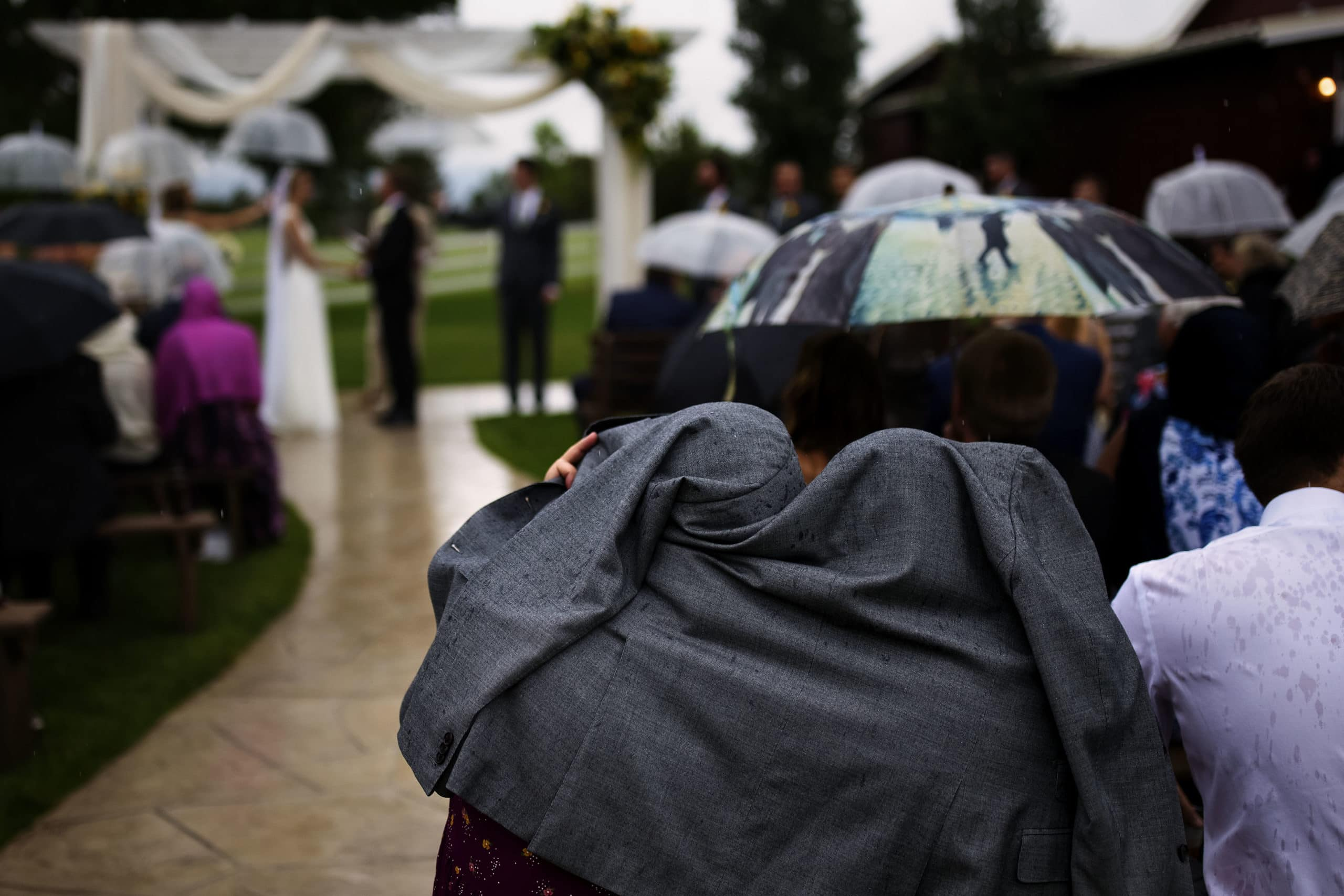 guests shelter under a coat during the wedding ceremony