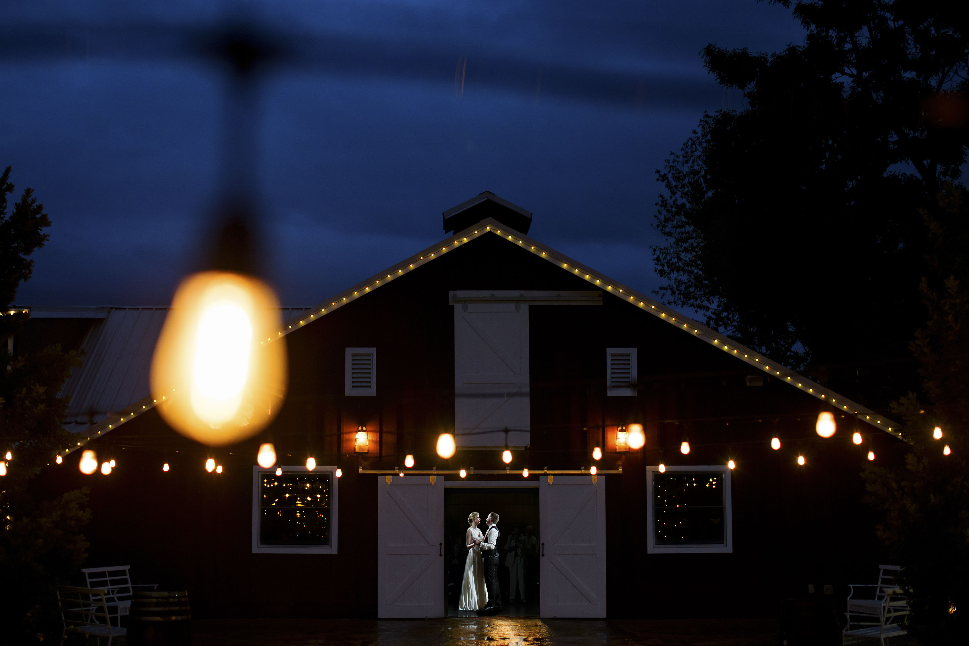 the bride and groom share their first dance at the wedding reception during twilight as market lights shine at the barn at raccoon creek
