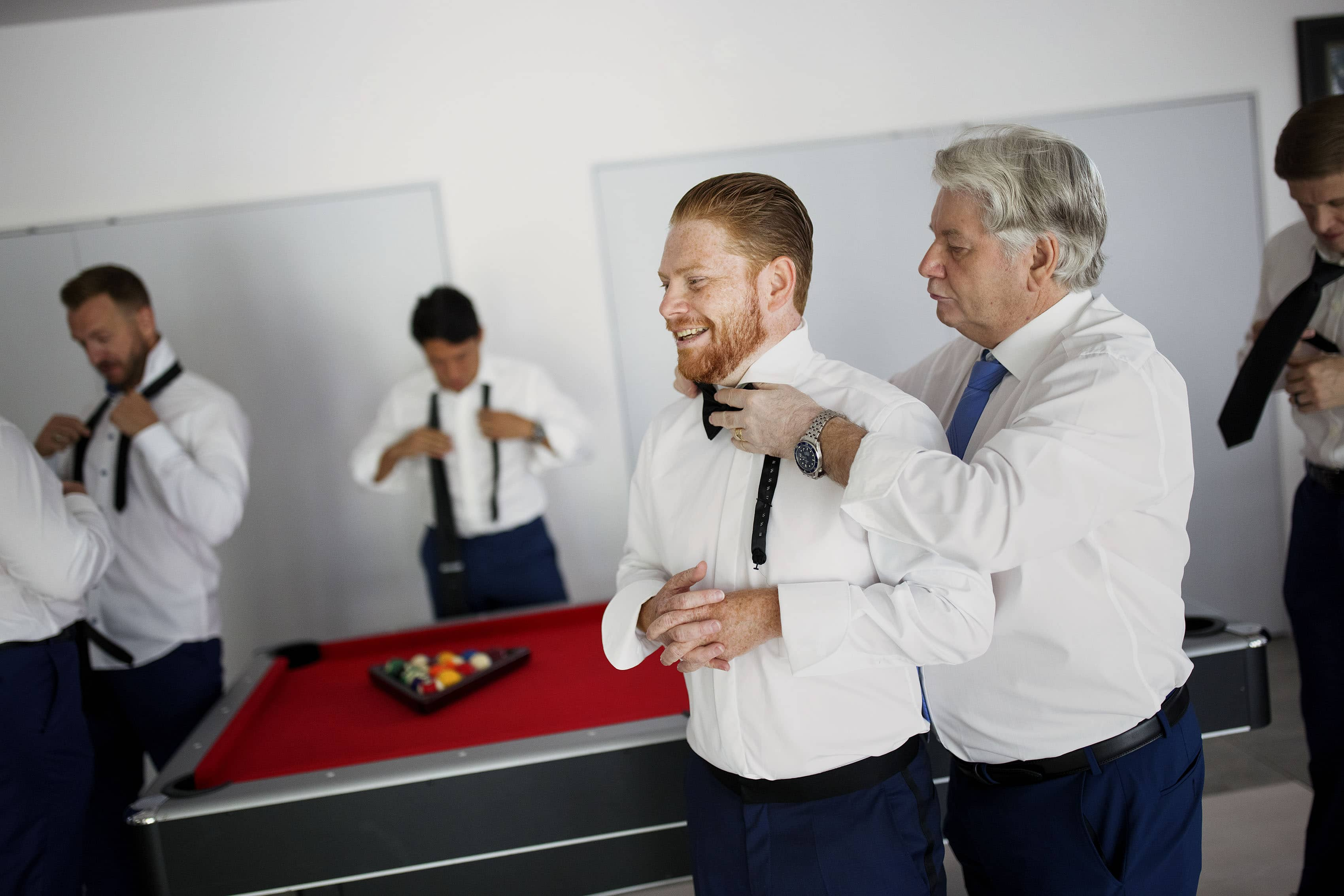 The groom gets some help with his tie