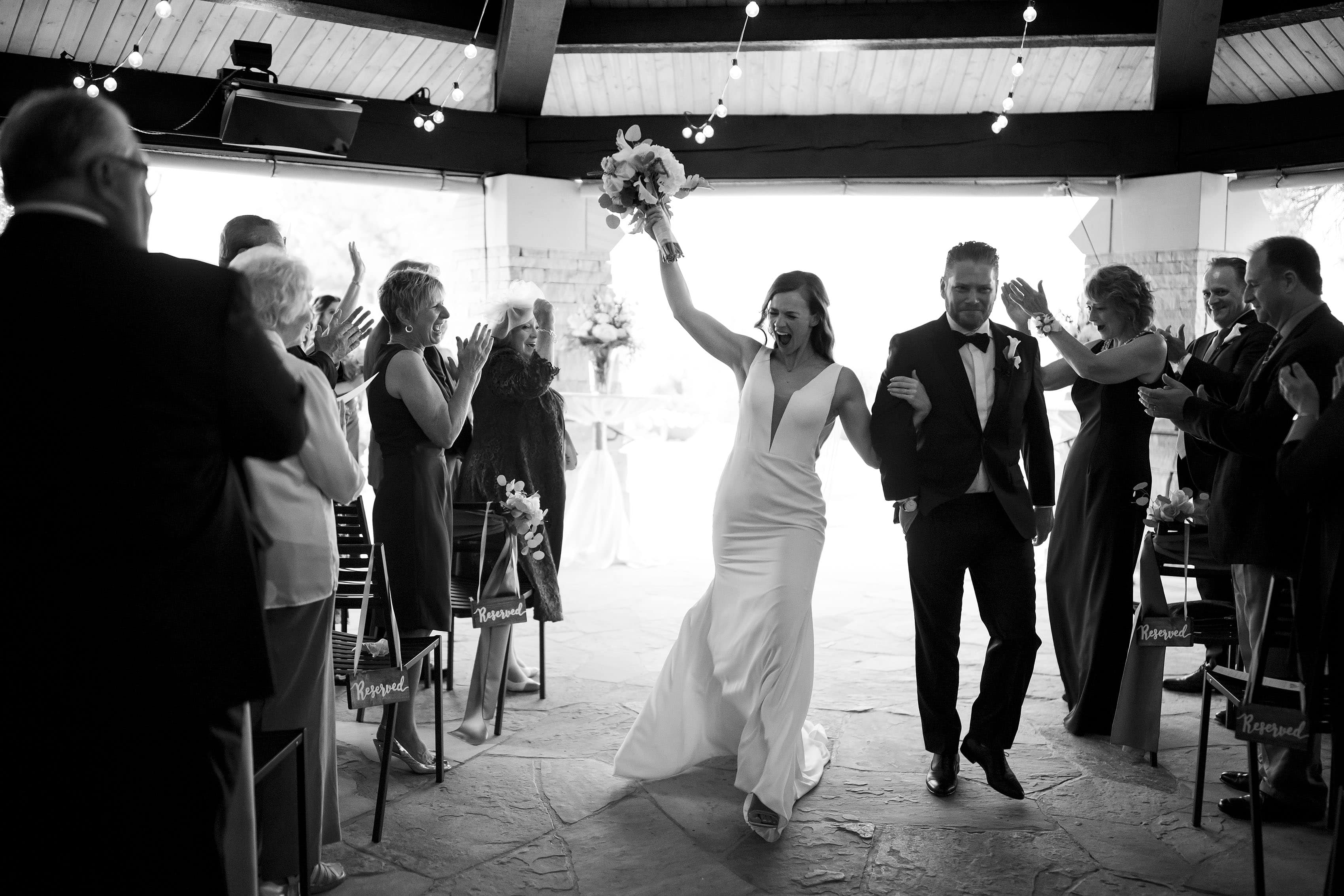 The bride and groom cheer after being announced as husband and wife during their Sanctuary wedding