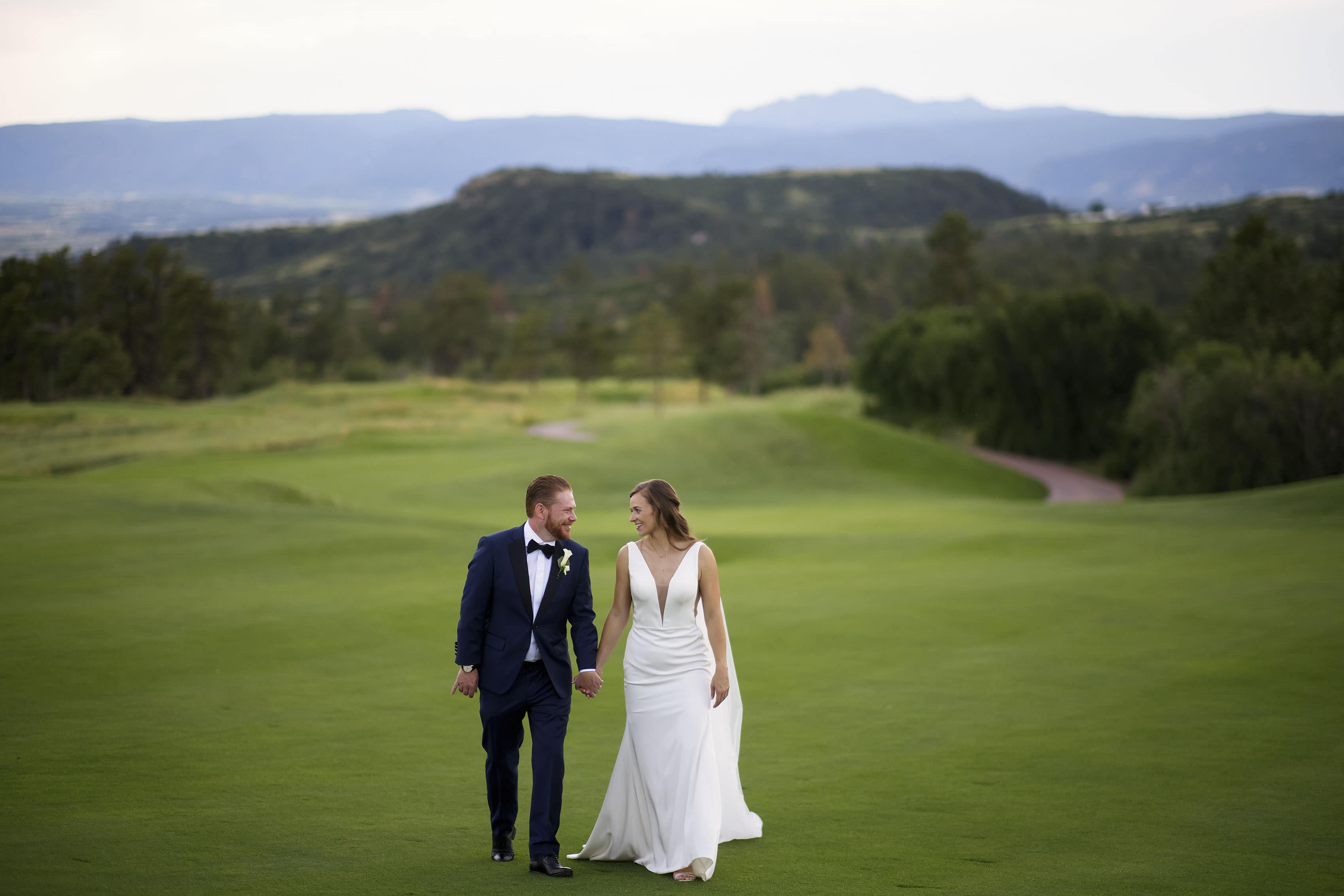 Casey and Darren walk along the 18th hole during their wedding at the Sanctuary