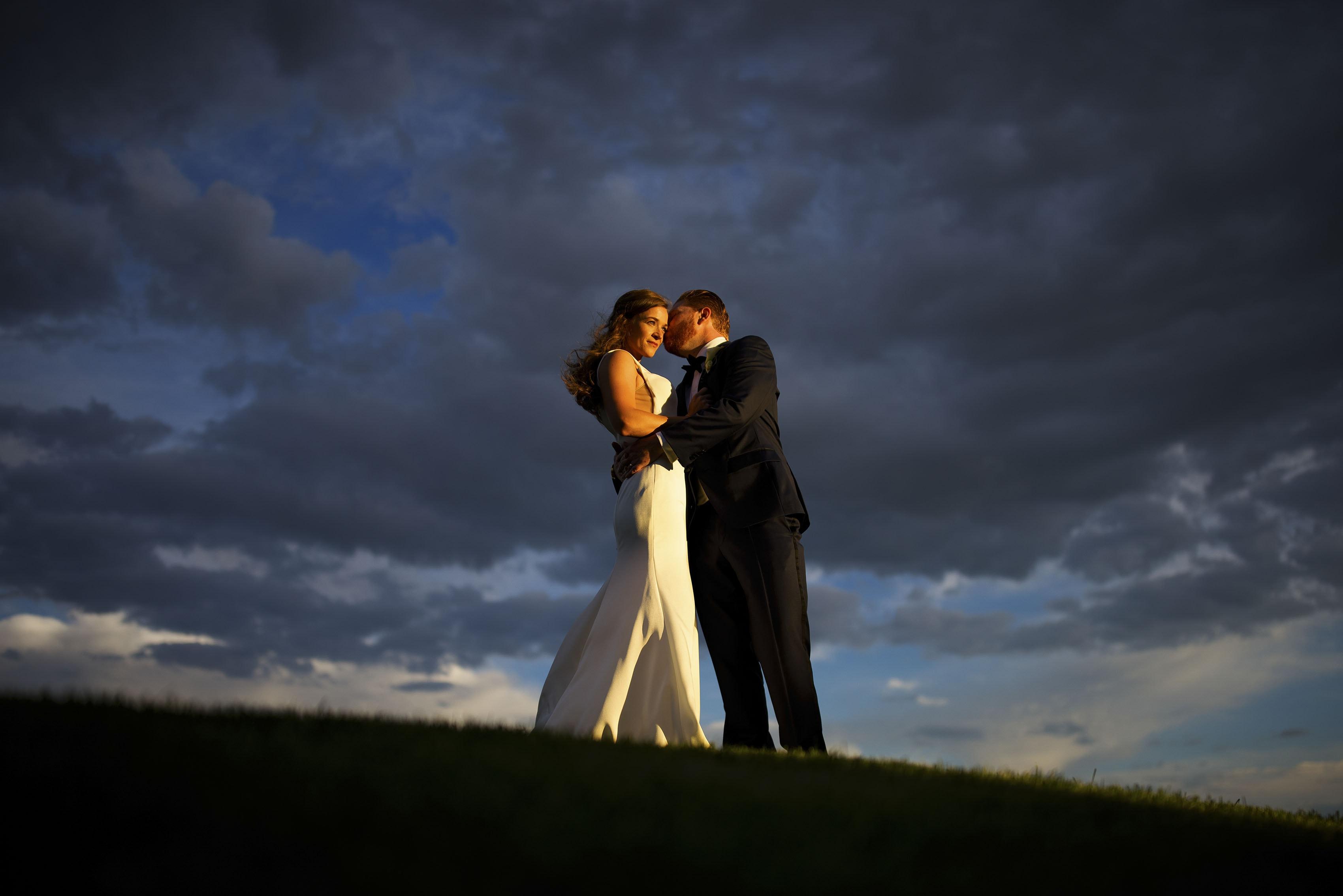 Darren kisses his bride during golden hour wedding portraits at Sanctuary Golf Course