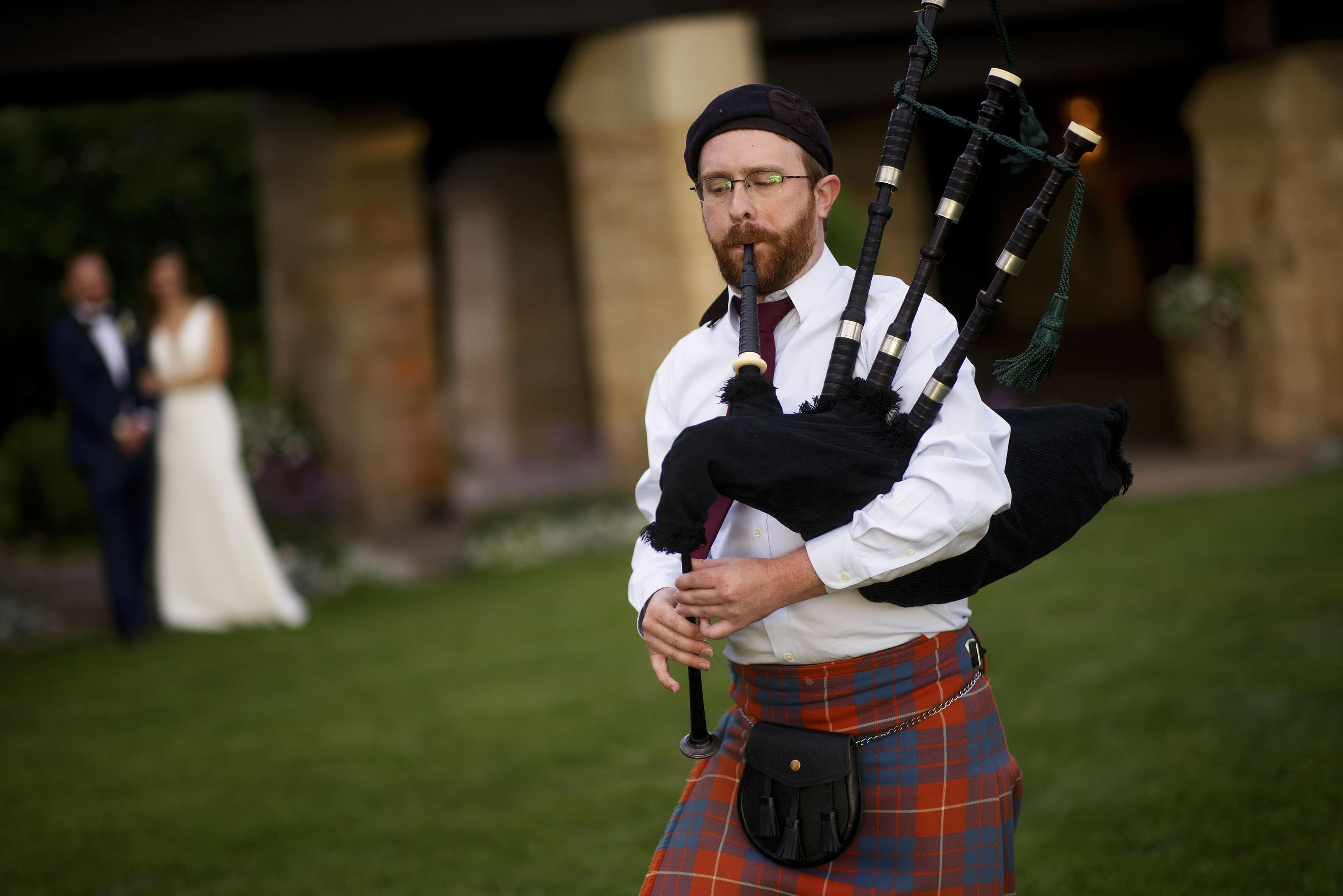 A bagpiper plays during Casey and DarrenÕs wedding reception at Sanctuary Golf Course