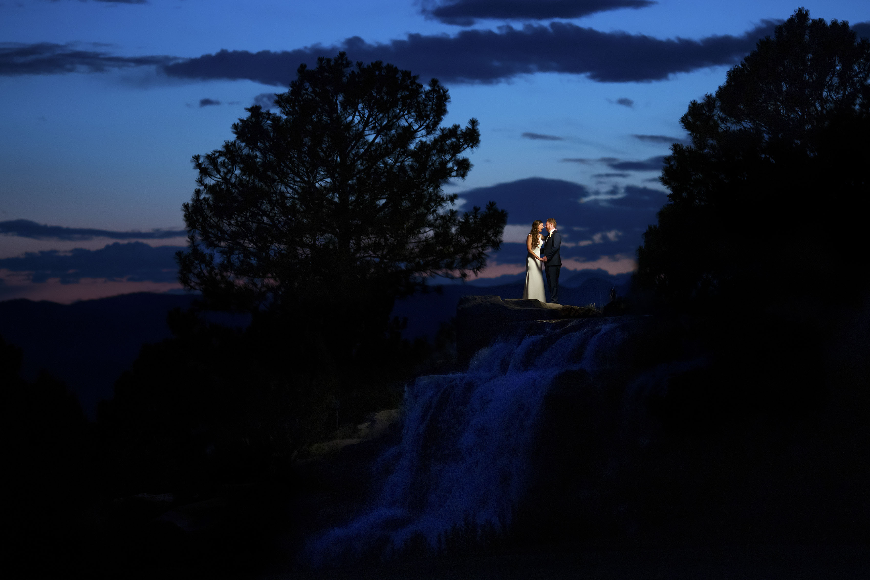 A married couple poses on the waterfall near the 18th hole at Sanctuary Golf Course