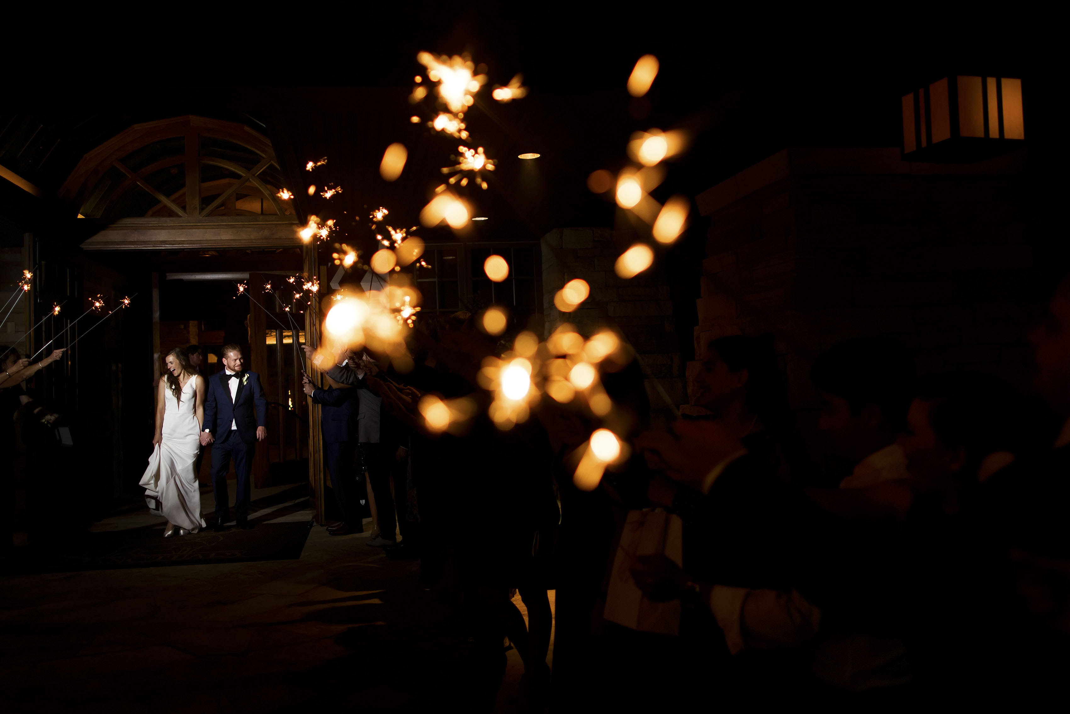 The bride and groom leave their wedding reception through a tunnel of sparklers at Sanctuary