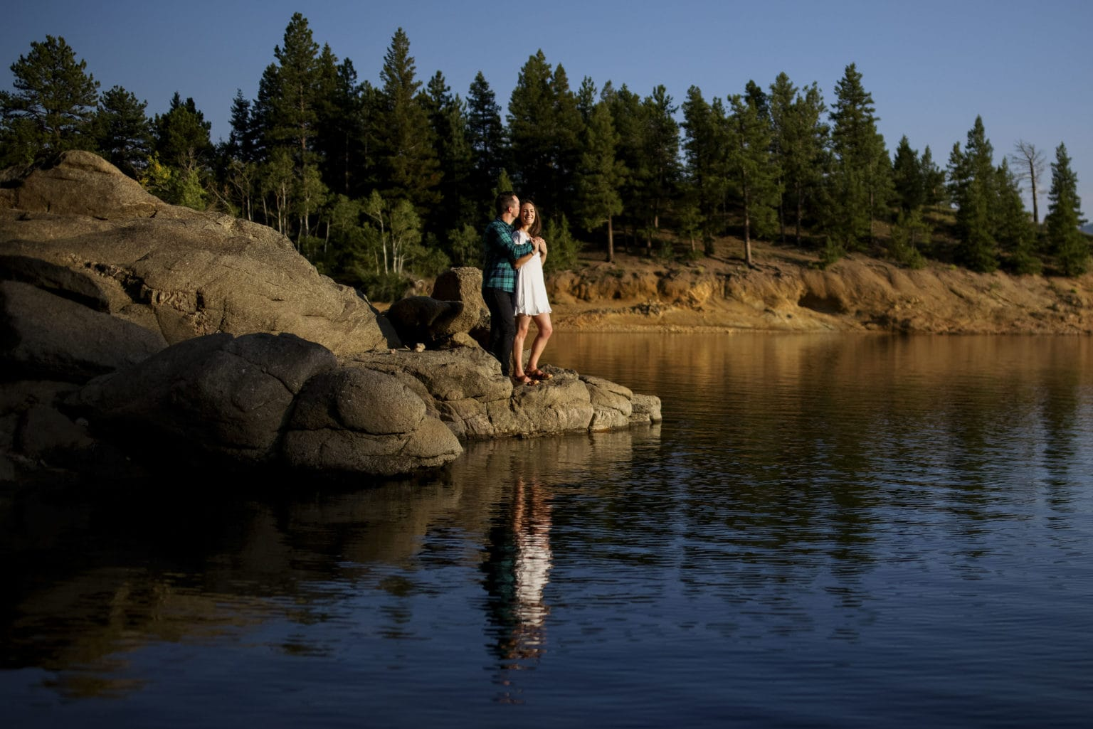 A couple embraces on a rock near Gross Reservoir in Boulder county during their engagement photos