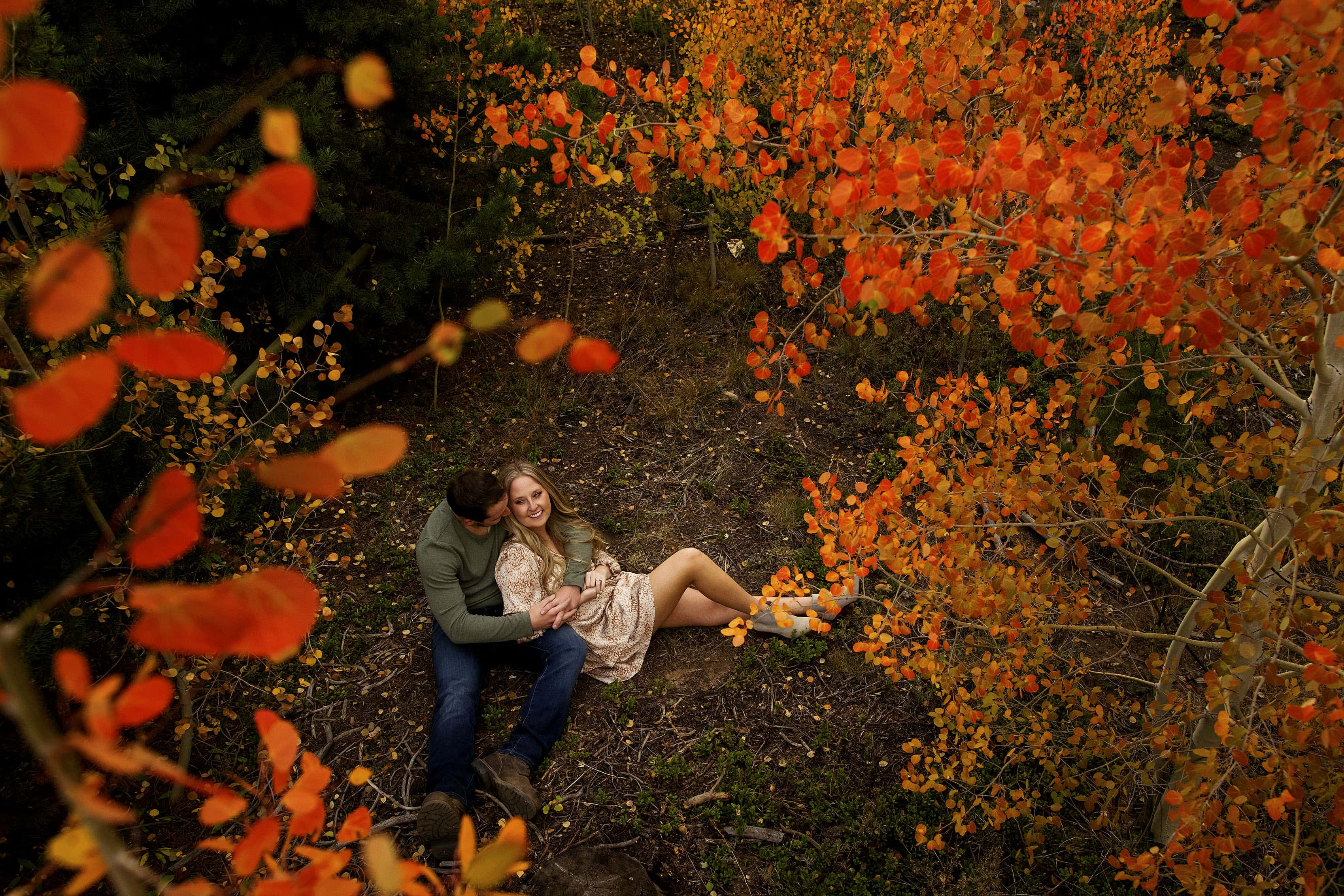 A couple sits on the ground surrounded by colorful aspen trees in Frisco, Colorado