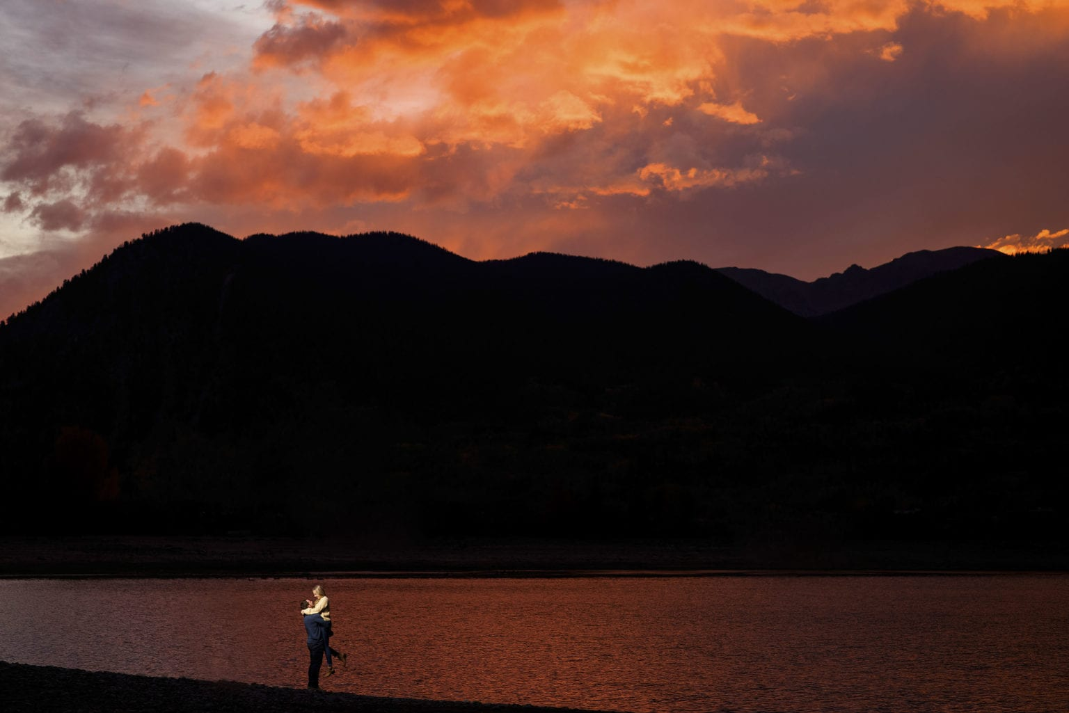 Chad picks Jamie up for a portrait near the edge of Dillon Reservoir in Summit County at sunset
