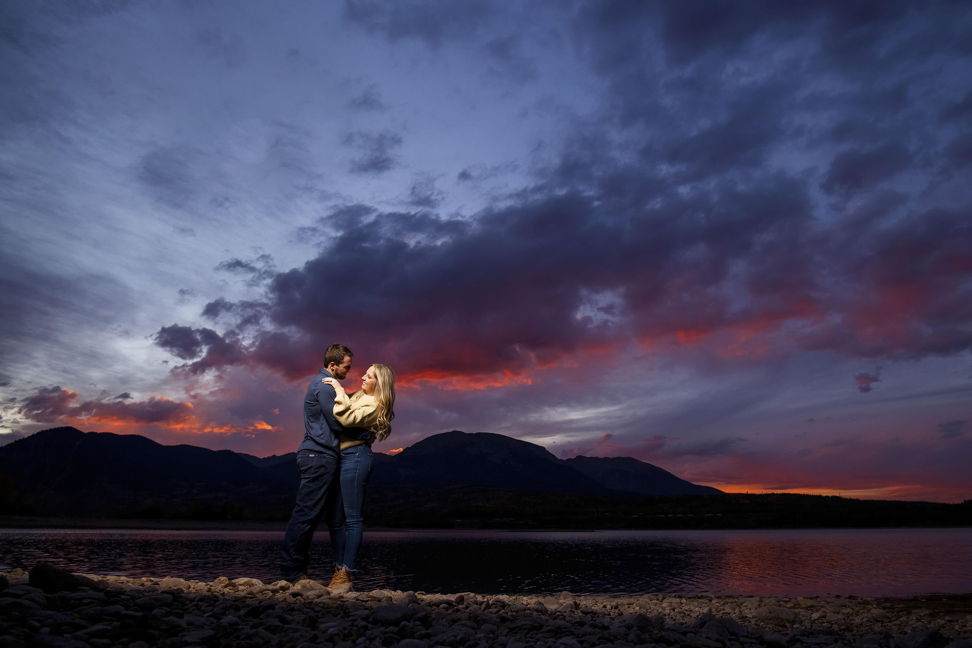Chad embraces Jamie near the edge of Dillon Reservoir at sunset during their engagement photos
